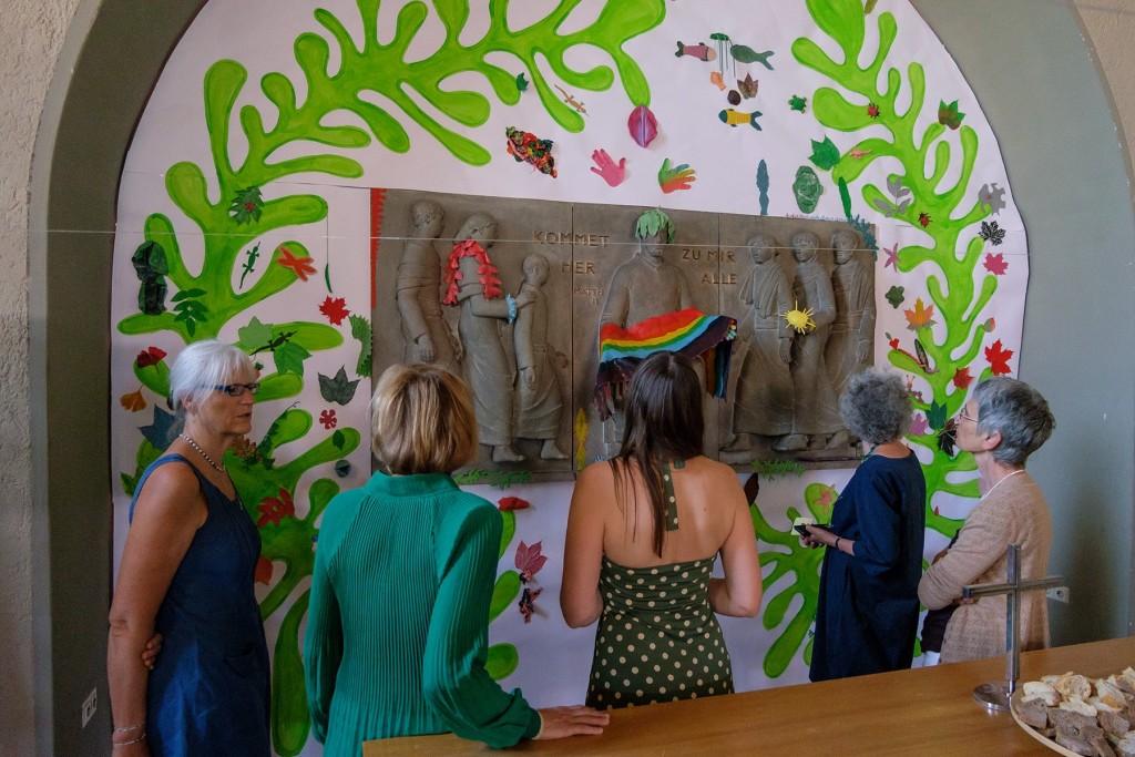 Besucher*innen betrachten die Altarwand mit Latexobjekten